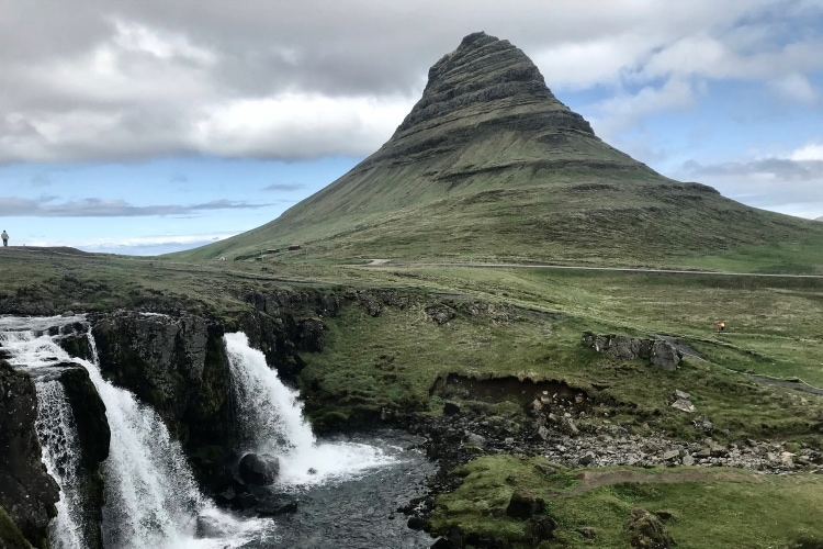 Steep ridgy green mountain with a waterfall in front at Kirkjufell in the Snaefellsnes peninsula