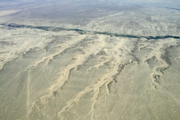 Canyons and a fertile valley in the Nazca desert seen from the air