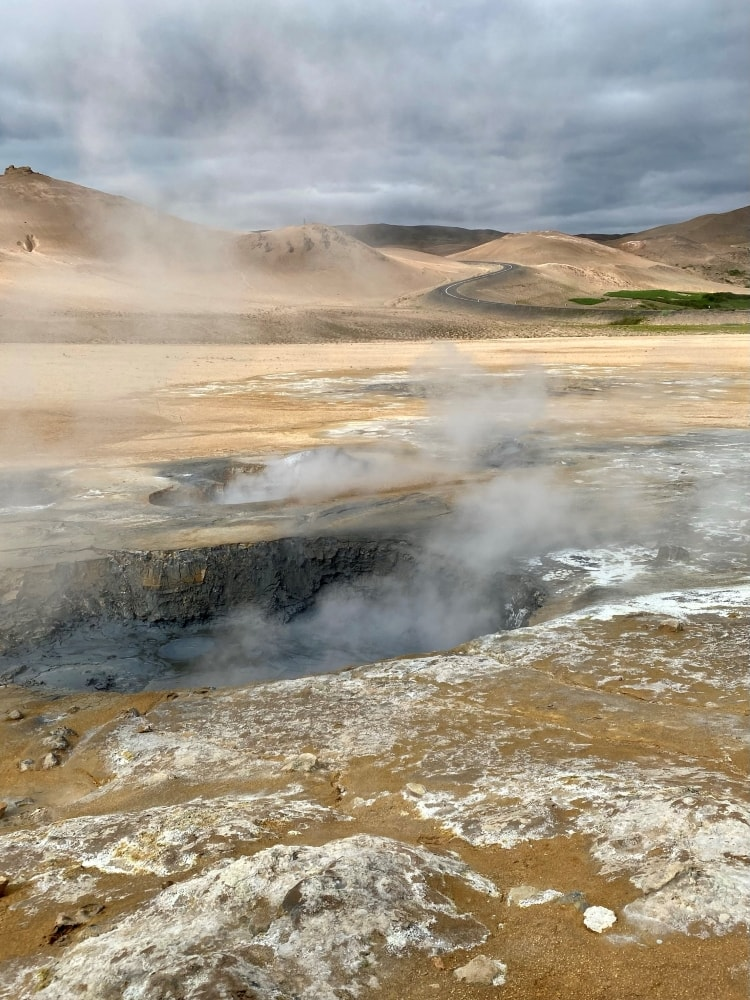 Boiling mud pits at Hverir geothermal area, with the ring road in the background