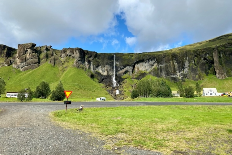 narrow waterfall over green cliffs by the ring road in iceland