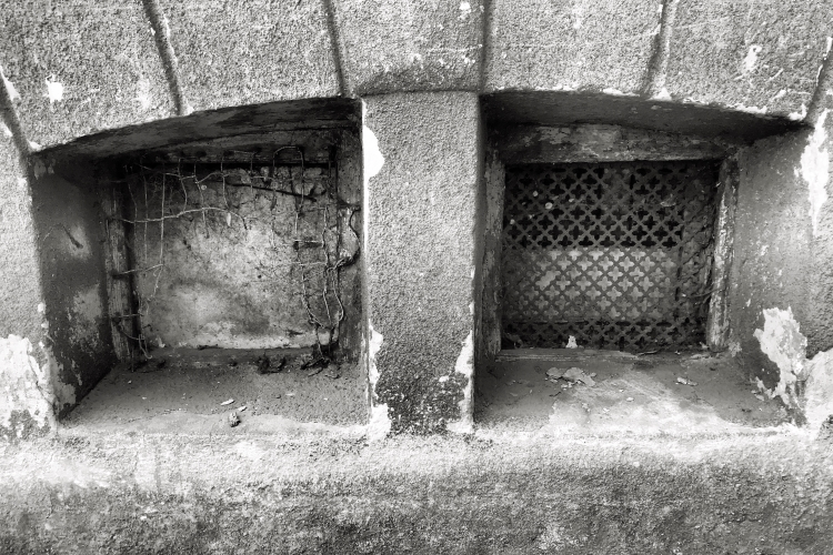 black and white image of crumbling and broken basement windows