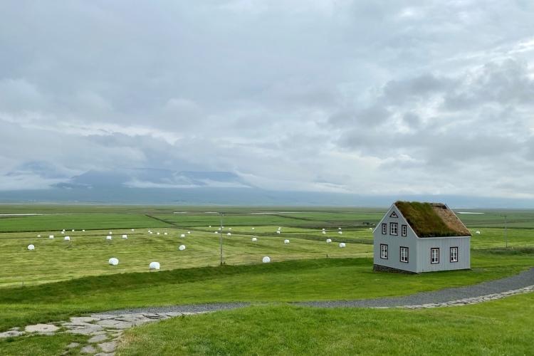 Views from Glaumbær turn roof farm across green farmland towards the cloud-shrouded mountains of the Trollaskagi peninsula