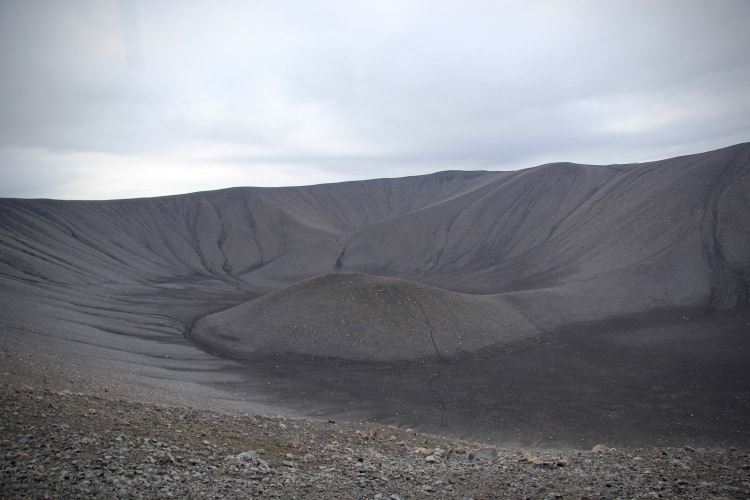 Looking into the dark gravelly crater of Hverfjall in north iceland