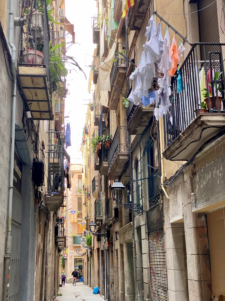 a narrow alleyway in Barcelona, with washing hanging, balconies and Catalan flags displayed