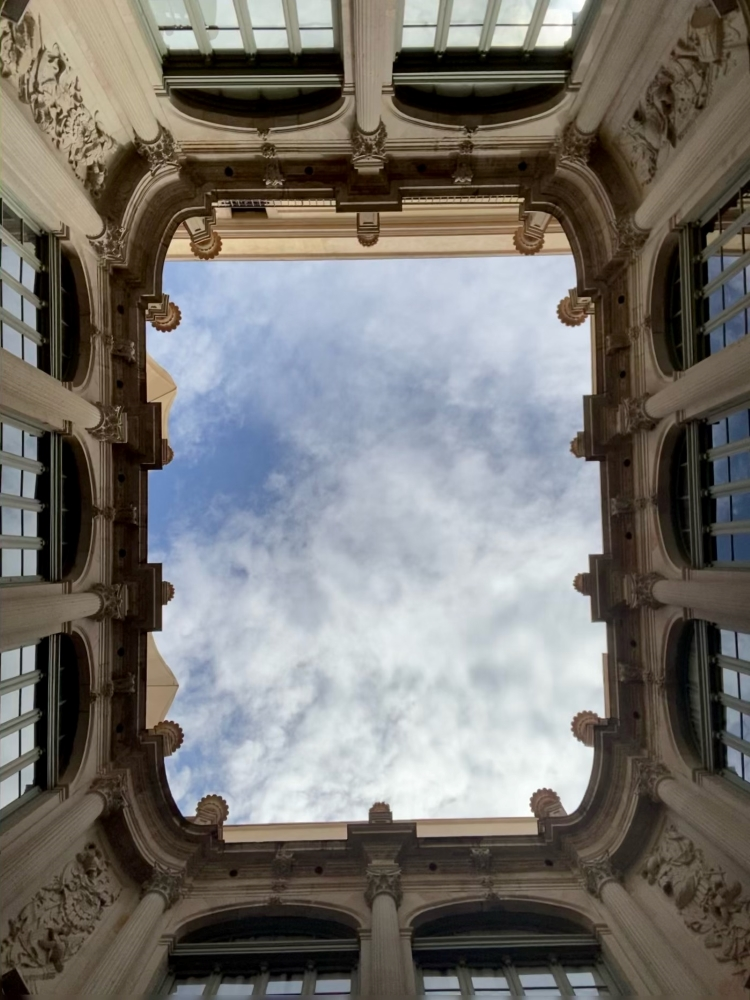 Ornate skylight framing clouds and blue sky in Barcelona